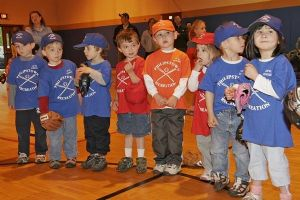 Young children in gym wearing baseball uniforms and gloves.